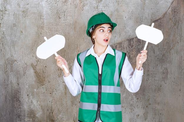 Vrouwelijke ingenieur in groen uniform en helm met twee bordjes in beide handen en ziet er verward uit