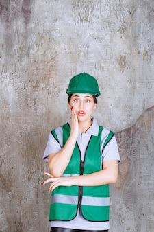 Vrouwelijke ingenieur in groen uniform en helm ziet er bang en doodsbang uit.