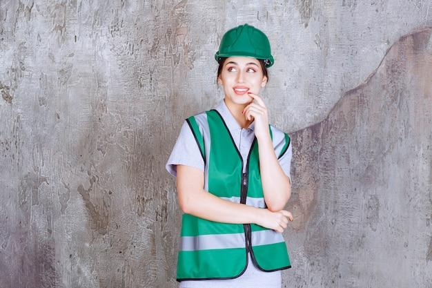 Vrouwelijke ingenieur in groen uniform en helm ziet er verward en attent uit.