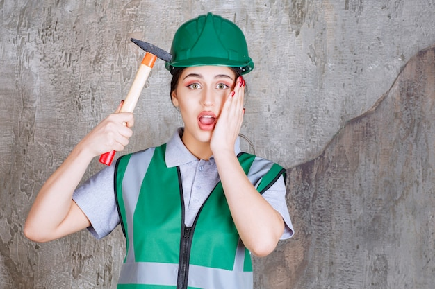 Vrouwelijke ingenieur in groene helm die een bijl met houten handvat vasthoudt voor reparatiewerk, ziet er verward uit en slaat haar helm met bijl.
