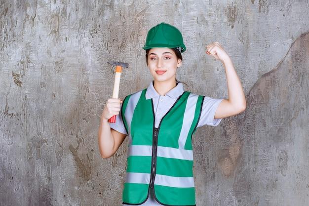 Vrouwelijke ingenieur in groene helm die een bijl met houten handvat vasthoudt voor reparatiewerkzaamheden en haar armspieren laat zien