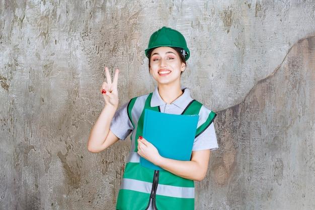 Vrouwelijke ingenieur in groene helm die een blauwe map vasthoudt en een positief handteken toont