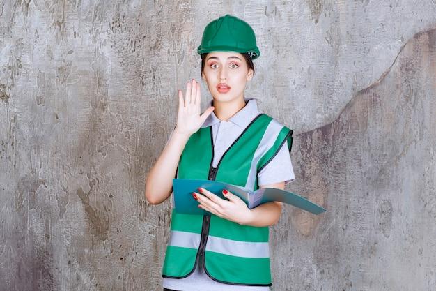 Vrouwelijke ingenieur in groene helm die een blauwe map vasthoudt en iets stopt.