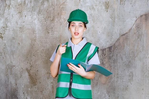 Vrouwelijke ingenieur in groene helm die een blauwe map vasthoudt en naar iemand in de buurt wijst