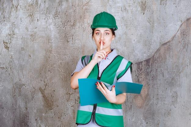 Vrouwelijke ingenieur in groene helm die een blauwe map vasthoudt en om stilte vraagt