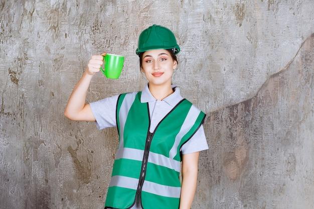 Vrouwelijke ingenieur in groene helm die een groene koffiemok houdt en glimlacht