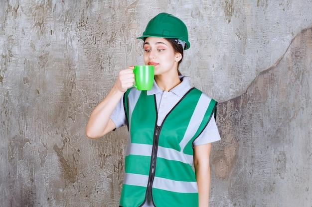 Vrouwelijke ingenieur in groene helm die een groene koffiemok houdt en het product ruikt.