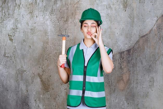 Vrouwelijke ingenieur in groene helm die een houten behandelde bijl voor een reparatiewerk houdt en positief handteken toont.