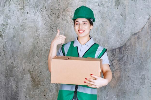 Vrouwelijke ingenieur in groene helm die een kartonnen doos vasthoudt en een tevredenheidsteken toont