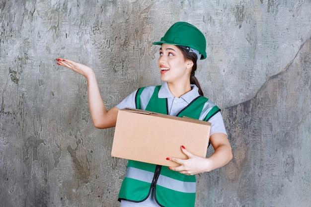 Vrouwelijke ingenieur in groene helm die een kartonnen doos vasthoudt en naar iemand in de buurt wijst