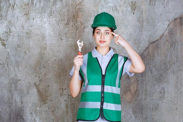 Vrouwelijke ingenieur in groene helm die een metalen moersleutel vasthoudt voor reparatiewerkzaamheden en nadenkt over nieuwe ideeën