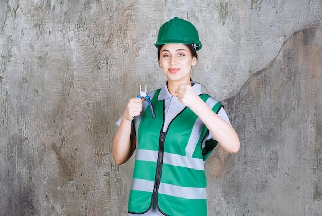 Vrouwelijke ingenieur in groene helm die een tang vasthoudt voor reparatiewerkzaamheden en haar vuist laat zien.