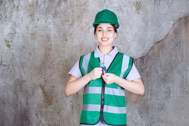 Vrouwelijke ingenieur in groene helm die een tang vasthoudt voor reparatiewerkzaamheden