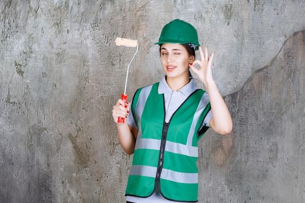 Vrouwelijke ingenieur in groene helm die een trimrol vasthoudt voor muurschildering en een positief handteken toont.
