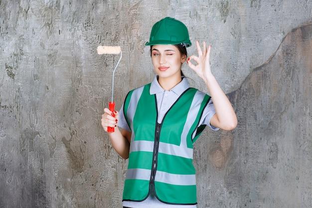 Vrouwelijke ingenieur in groene helm die een trimrol vasthoudt voor muurschildering en een positief handteken toont