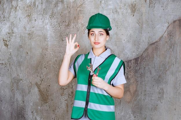 Vrouwelijke ingenieur in groene helm die metalen moersleutel vasthoudt voor reparatiewerkzaamheden en een positief handteken toont.