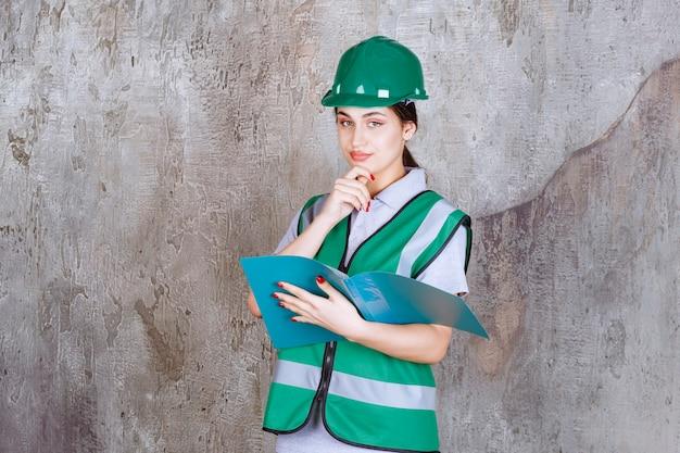 Vrouwelijke ingenieur in groene helm met een blauwe map en ziet er verward en attent uit.