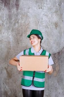 Vrouwelijke ingenieur in groene helm met een kartonnen doos