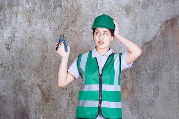 Vrouwelijke ingenieur in groene helm met een tang voor reparatiewerkzaamheden en ziet er verward en attent uit