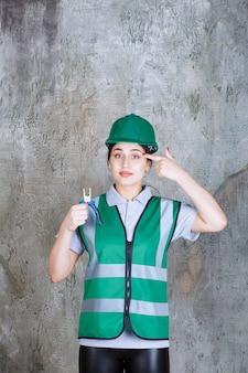 Vrouwelijke ingenieur in groene helm met een tang voor reparatiewerkzaamheden en ziet er verward en attent uit.