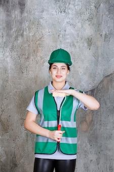 Vrouwelijke ingenieur in groene helm met een trimrol voor muurschildering.