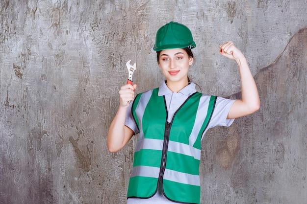 Vrouwelijke ingenieur in groene helm met metalen moersleutel voor reparatiewerkzaamheden en toont haar vuist.