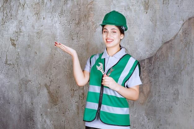 Vrouwelijke ingenieur in groene helm met metalen moersleutel voor reparatiewerkzaamheden en wijzend op de betonnen muur erachter.