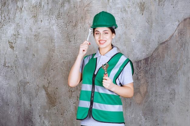 Vrouwelijke ingenieur in groene helm met metalen moersleutel voor reparatiewerkzaamheden en ziet er verward en attent uit.