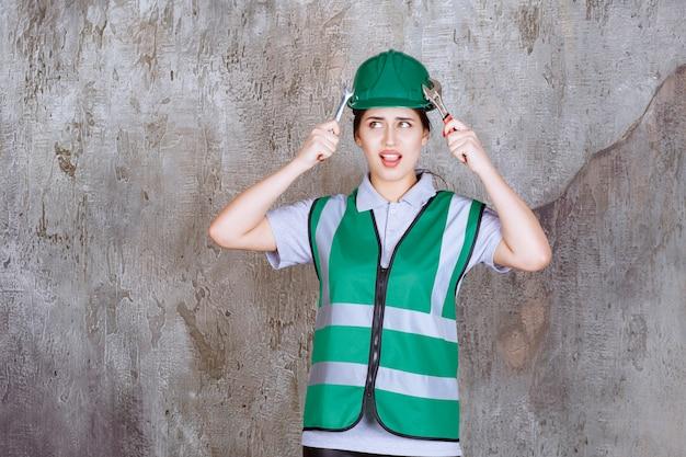 Vrouwelijke ingenieur in groene helm met metalen moersleutel voor reparatiewerkzaamheden, raakt haar helm en ziet er doodsbang uit.
