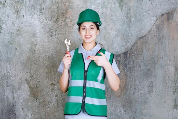 Vrouwelijke ingenieur in groene helm met metalen moersleutel voor reparatiewerkzaamheden.