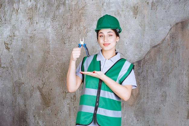 Vrouwelijke ingenieur in groene helm met tang voor reparatiewerkzaamheden.