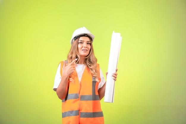 Vrouwelijke ingenieur in helm en uitrusting die het bouwplan vasthoudt en erop wijst.