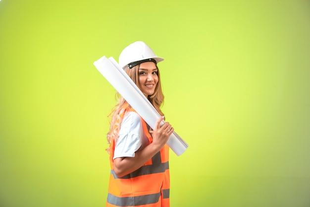 Vrouwelijke ingenieur in helm en vistuig die het bouwplan houden en glimlachen