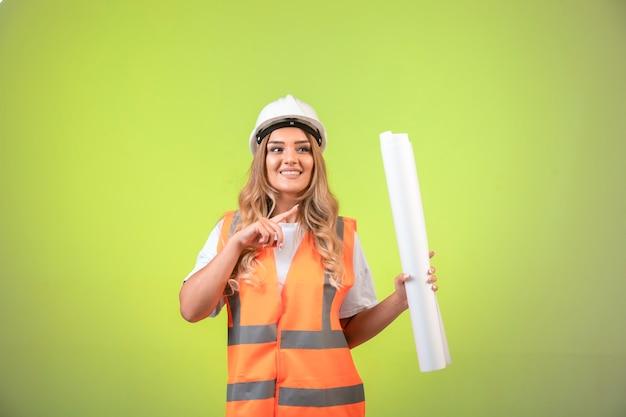 Vrouwelijke ingenieur in helm en vistuig houdt het bouwplan vast en toont het.