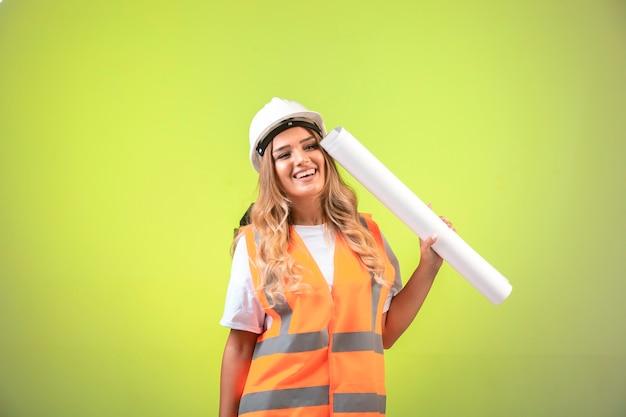 Vrouwelijke ingenieur in helm en vistuig houdt het bouwplan vast en ziet er positief uit.