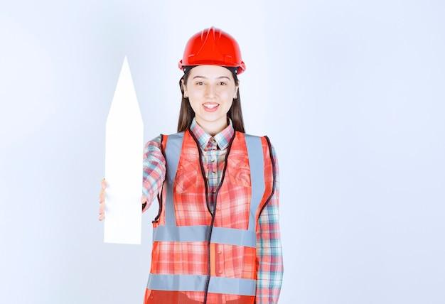 Vrouwelijke ingenieur in rode helm die een pijl houdt die hierboven wijst.