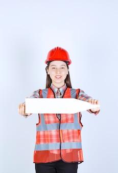 Vrouwelijke ingenieur in rode helm met een pijl die naar rechts wijst.