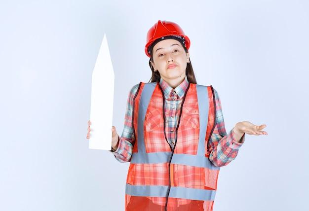 Vrouwelijke ingenieur in rode helm met een pijl naar boven gericht en ziet er verward uit.