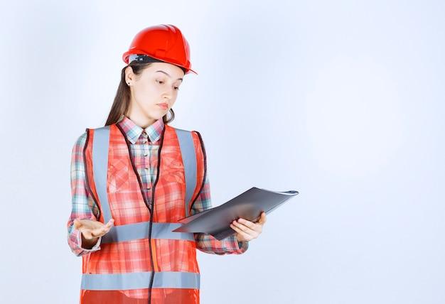 Vrouwelijke ingenieur in rode helm met een zwart projectplan en ziet er verward uit.