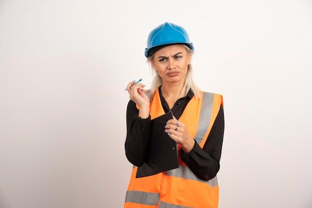 Vrouwelijke ingenieur in uniform ziet er ontevreden uit. hoge kwaliteit foto