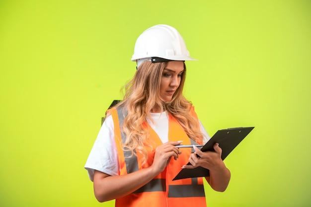 Vrouwelijke ingenieur in witte helm en uitrusting die de controlelijst vasthoudt en naar het rapport kijkt.