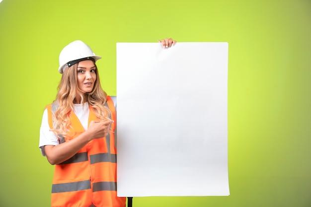 Vrouwelijke ingenieur in witte helm en uitrusting die het bouwplan toont en het uitlegt.