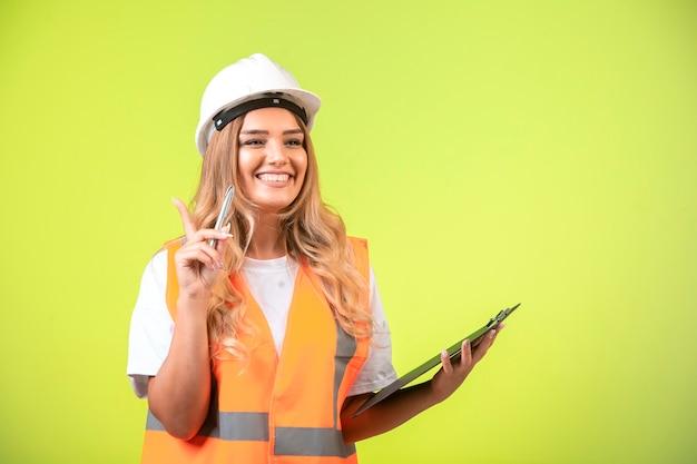 Vrouwelijke ingenieur in witte helm en uitrusting houdt de checklist vast en voelt zich zelfverzekerd.