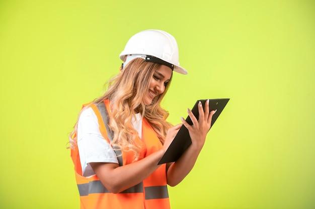 Vrouwelijke ingenieur in witte helm en versnelling die de controlelijst vasthoudt en aantekeningen maakt.