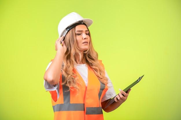 Vrouwelijke ingenieur in witte helm en versnelling die de controlelijst vasthoudt en droomt.