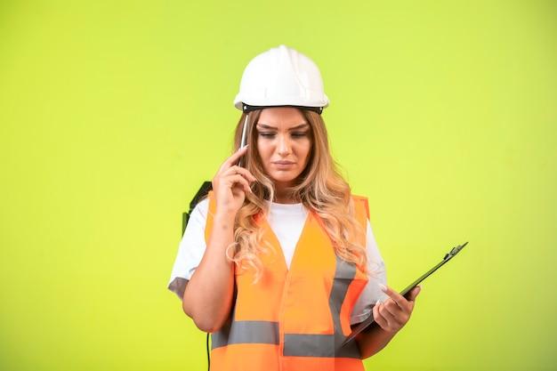 Vrouwelijke ingenieur in witte helm en versnelling die de controlelijst vasthoudt en probeert te onthouden.