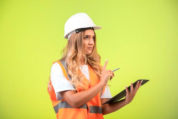 Vrouwelijke ingenieur in witte helm en versnelling met de checklist en vraagt om spraak.