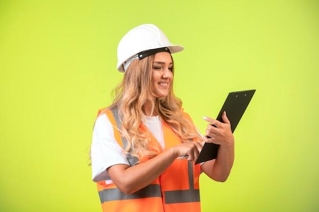 Vrouwelijke ingenieur in witte helm en versnelling met de checklist.