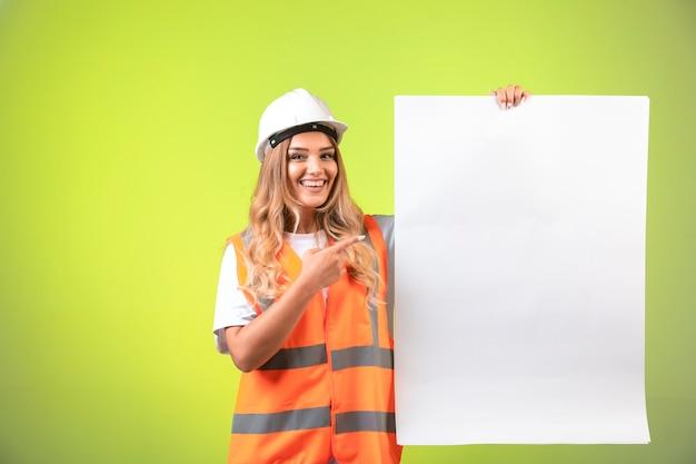 Vrouwelijke ingenieur in witte helm en versnelling presenteren het bouwplan.