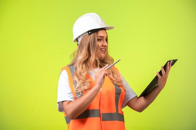 Vrouwelijke ingenieur in witte helm en vistuig die de controlelijst vasthoudt en corrigeert.